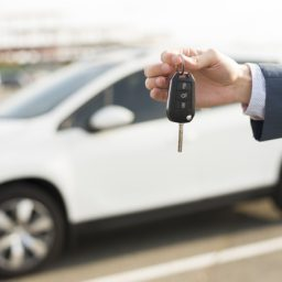 businessman-with-keys-front-car_23-2147986531