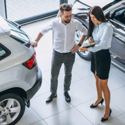 salesman-woman-looking-car-car-showroom_1303-13643