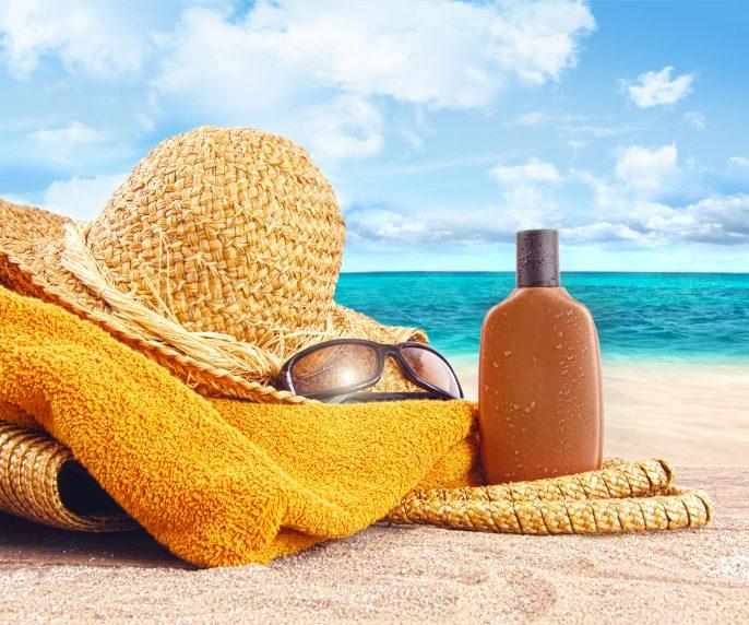 Suntan lotion, straw hat at the beach